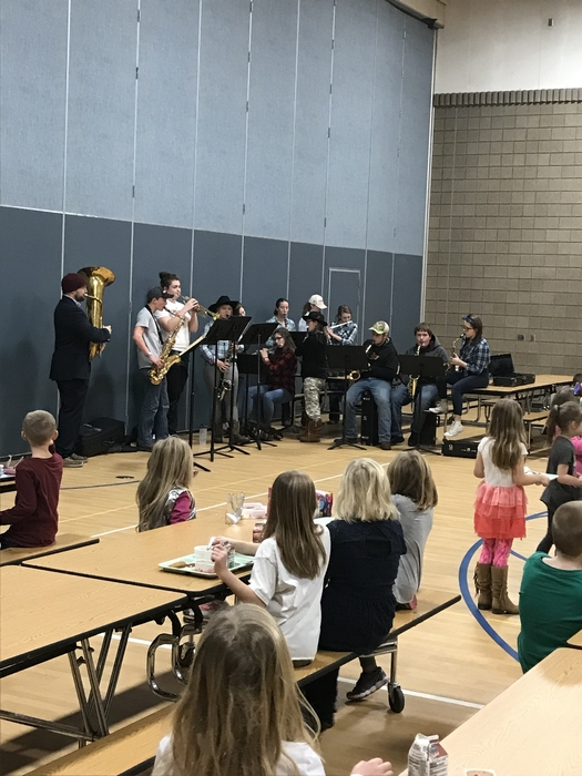 High school band members playing holiday tunes for elementary students having lunch