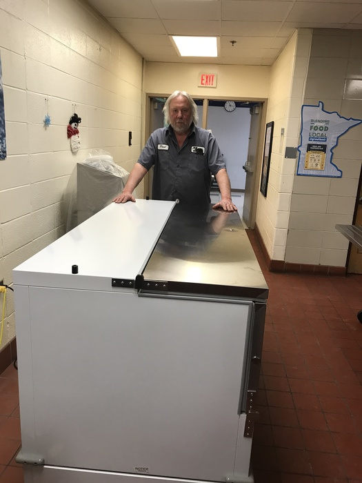Custodian Paul at the High School is displaying the new cooler purchased with the grant.